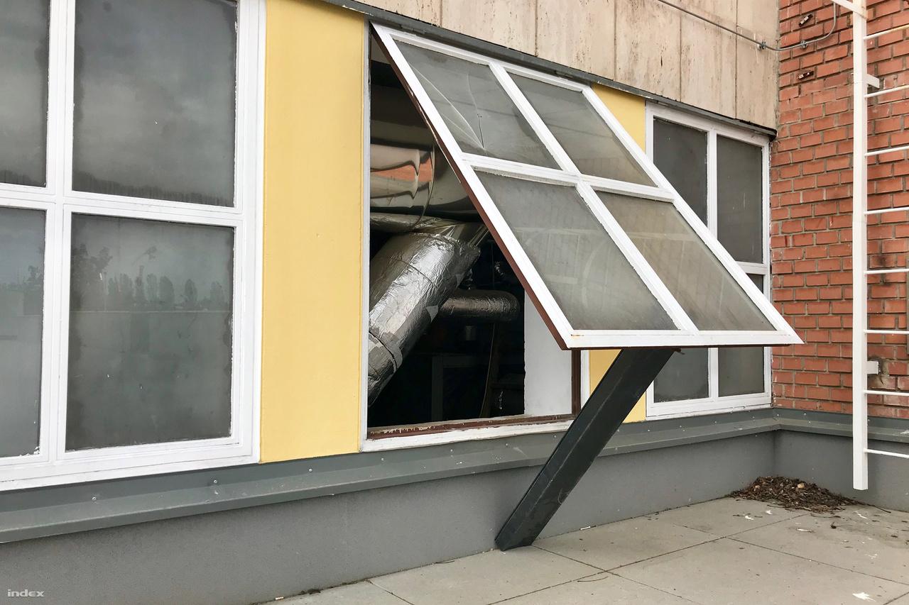 Ha meleg van, szellőztetni kell. Az ablak nyitva tartásának praktikus módja a kitámasztás egyméteres vasszelvény segítségével. Majd lesz egyszerűbb megoldás is, ha valaki végre rendesen kitöri azt a bal felső táblát.