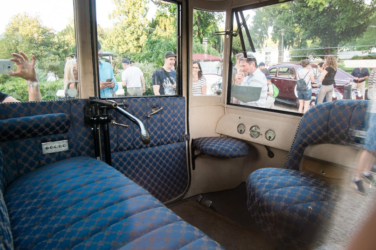 Nem igaz, hogy nem kellett valamiféle kisgépvezetői tanfolyam az 1918-as Detroit Electric 75 sokféle kütyüjének kezeléséhez. Azt mindenesetre megtudtuk, hogy a hosszú kar a kormány, a rövid a sebességszabályzó. Az idén pont százéves villanyautó életképességét bizonyítja, hogy amikor a vele szinte egyidős EMF-Studebakert nem lehetett reggel beindítani, ez húzta ki a kiállításra a füredi mélygarázsból. Lazán.