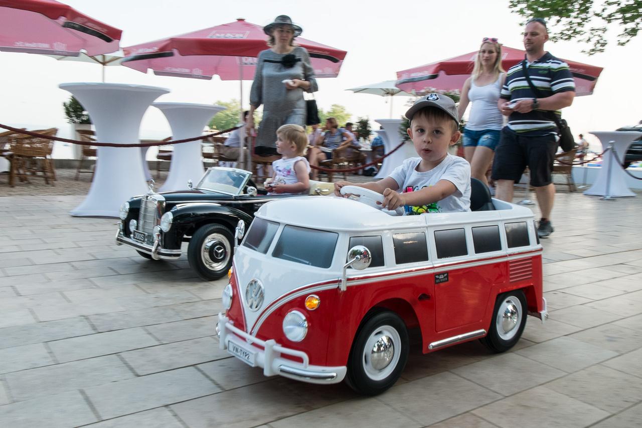 A Concours VIP-zug környékén a terítőt abrosznak, a hűtőszerkrényt fridzsidernek, a pedálos gokartot villanyhajtású Mercedes 300S-nek és VW Sambának mondják.
