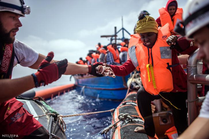 Menekülteknek segítenek az SOS Mediterranee civil szervezet Aquarius nevű hajója legénységének tagjai a Földközi-tengeren 2018. április 21-én. Az Aquarius mintegy 250 csónakban utazó illegális bevándorlót vett a fedélzetére a líbiai partoktól mintegy 50 kilométerre.