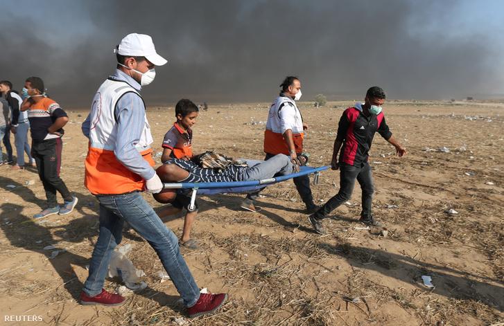 Sérült palesztin tüntetők cipelnek a társai a gázai övezetben május 15-én.
