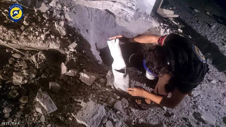 A Szíriai Polgári Védelem idlibi szervezete által közreadott képen egy feltehetően klórgáz tárolására alkalmas dobozt vizsgál egy férfi az északnyugat-szíriai Idlíb tartomány Szarakib nevű településén 2016. augusztus 2-án. A polgári védelem egyik szóvivője szerint egy jelzés nélküli helikopter mérges gázzal töltött konténereket dobott le az éjszaka folyamán a településre, amelynek közelében az előző nap lelőttek egy orosz katonai szállító helikoptert.