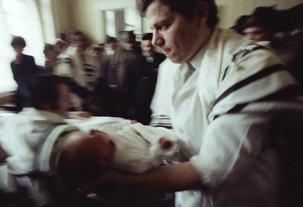 Féner Tamás fényképei a születéstől a halálig mutatják be a zsidó vallás rítusait. Az újszülött kisfiúkon a születés utáni nyolcadik napon végzik el a körülmetélést, amelyet Ábrahám először fián, a később majdnem feláldozott Izsákon hajtott végre.  Mózes első könyve szerint Ábrahám ekkor kereken száz éves volt.