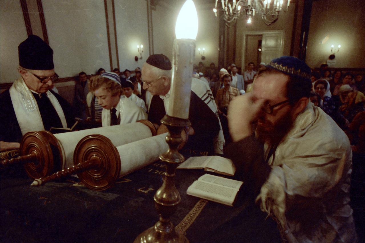 A zsidó vallás szerint a fiúk 13 évesen válnak nagykorúvá, ekkor járulnak először a Tóra elé, majd olvasnak fel belőle egy részletet. A képen egy bár micvá látható olvasás közben, akire hamarosan érvényesek lesznek a zsidó  parancsolatok. Magyarországon régebben dióval dobálták meg a gyereket, a dió ugyanis a termékenység szimbóluma.