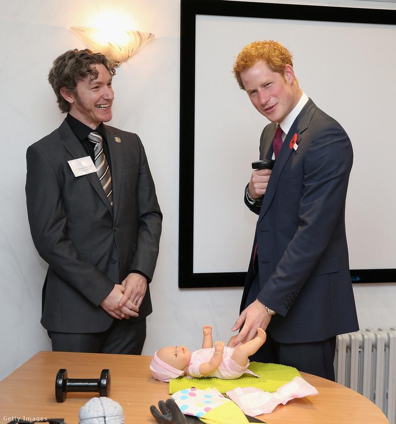 Harry herceg itt megkísérel fél kézzel tisztába tenni egy műanyaggyereket.
