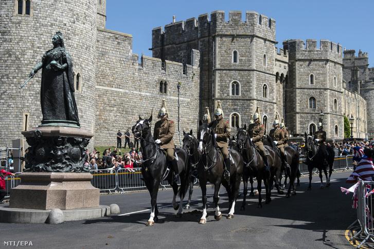 A brit királyi hadsereg egyik lovas díszegysége a windsori kastély mellett halad el Harry herceg és Meghan Markle közelgő esküvője előtt tartott ceremoniális főpróbán 2018. május 17-én.