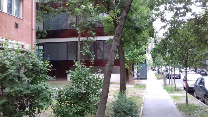 Lakóház előkerttel és a szomszédos irodaház előretolt homlokzata