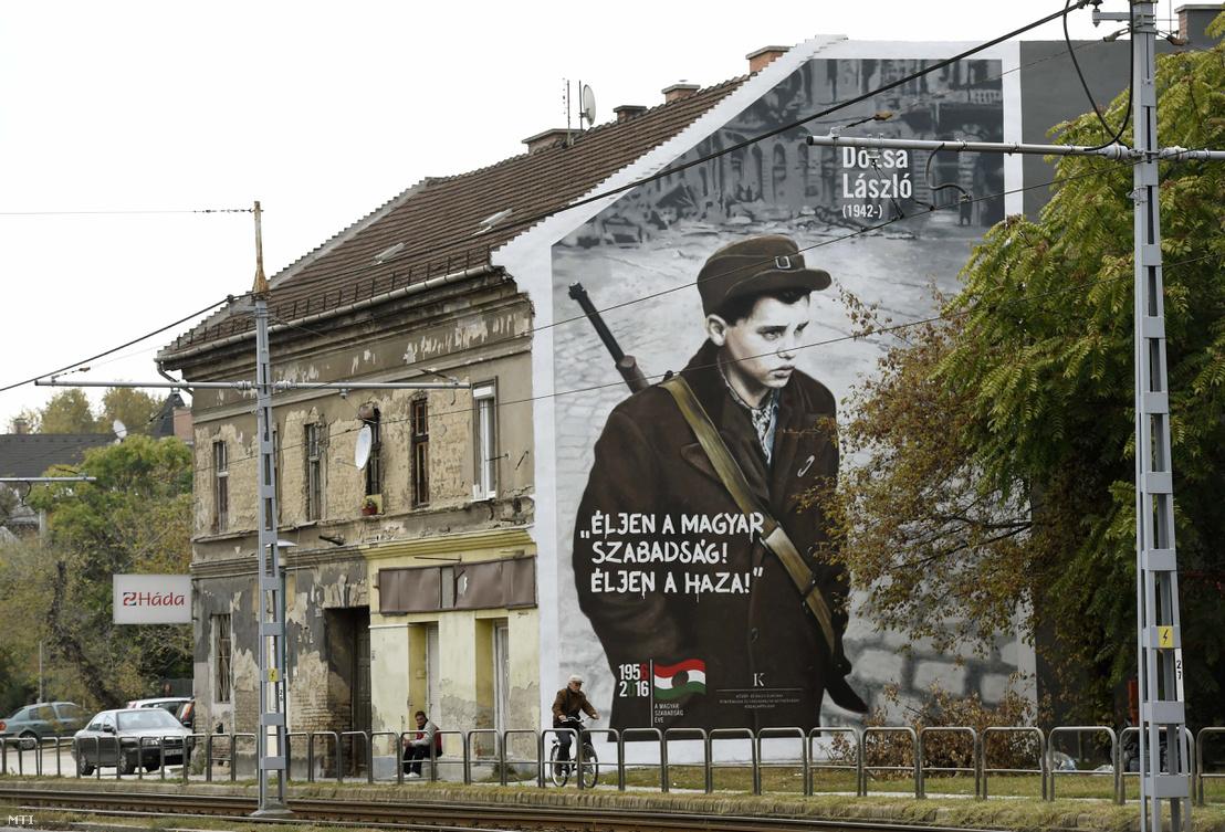 """Szó szerint idéznénk az MTI képaláírását: """"Az 1956-os forradalom és szabadságharc 60. évfordulója alkalmából készített Dózsa Lászlót ábrázoló falfestés a XIV. kerület Nagy Lajos király útja 155. szám alatti társasház falán 2016. október 13-án. Az akkor 14 éves forradalmárt az ÁVH-sok úgy megverték hogy a klinikai halál állapotába került majd tömegsírba temették. A sírásó észrevette hogy mozog és a tiltás ellenére megmentette attól hogy élve eltemessék. A kádári megtorlás során nem találták meg mivel a nyilvántartásban kartonján az szerepelt hogy meghalt és eltemették."""""""