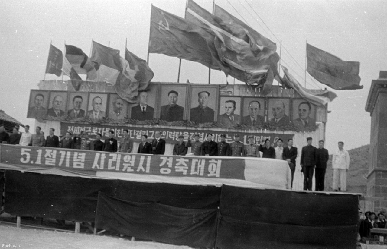 Dísztribünről nézik a felvonulókat a politikai vezetők. Mögöttük a baráti kommunista országok (NDK, Csehszlovákia, Vietnam, stb) vezetőinek portréi, középen természetesen Kim Ir Szen, Észak-Korea alapítója, miniszterelnöke, elnöke, teljhatalmú ura. Mellette Nyikita Hruscsov és Mao Ce-tung, a Szovjetunió és a Kínai Népköztársaság vezetői. Jobbról a második pedig nem más, mint maga Rákosi Mátyás, fölötte a magyar zászlót kissé félárbócra ereszkedve tépi a szél.