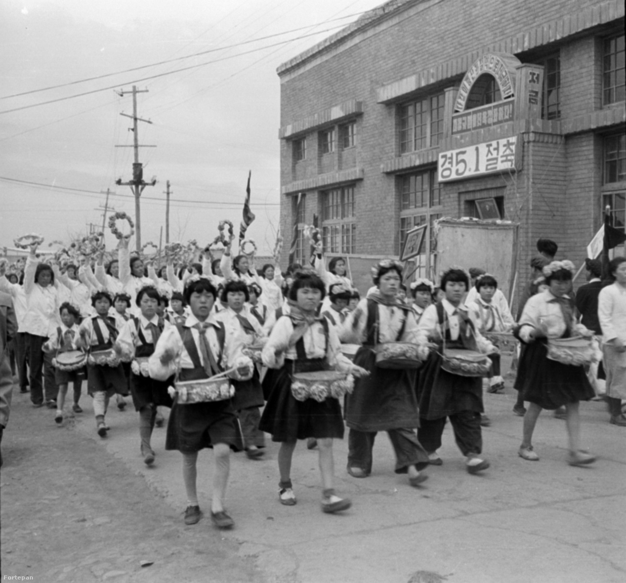 Észak-koreai úttörőlányok felvonulása, mögöttük középiskolás korú lányok lengetnek koszorúkat.