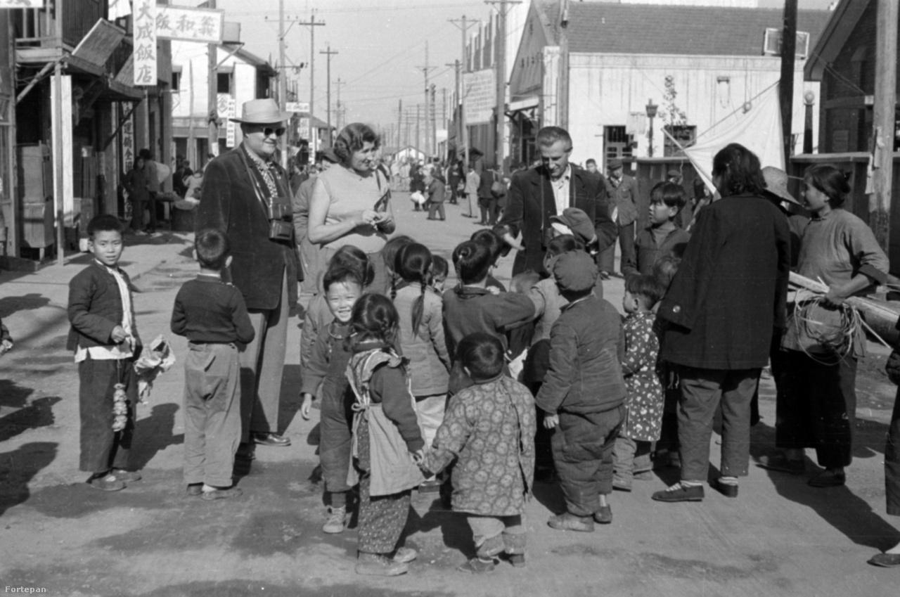 Kínai utcakép, gyerekhaddal. A sok számmal nagyobb, feltehetőleg már több, nagyobb testvér által is hordott kopottas ruhák meglehetős szegénységről árulkodnak.