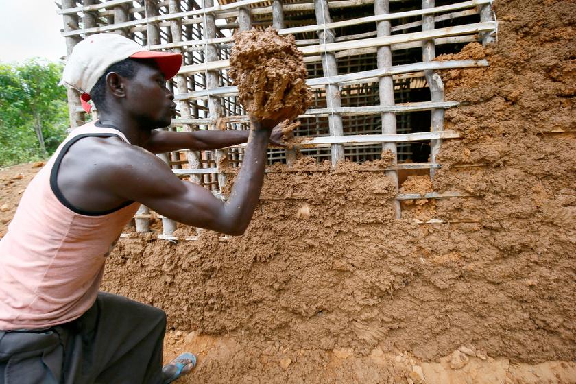 Libériai férfi sárral tölti ki egy épülő ház faszerkezetének réseit a libériai Grand Bassa megyei Malcolmban 2018. május 19-én.