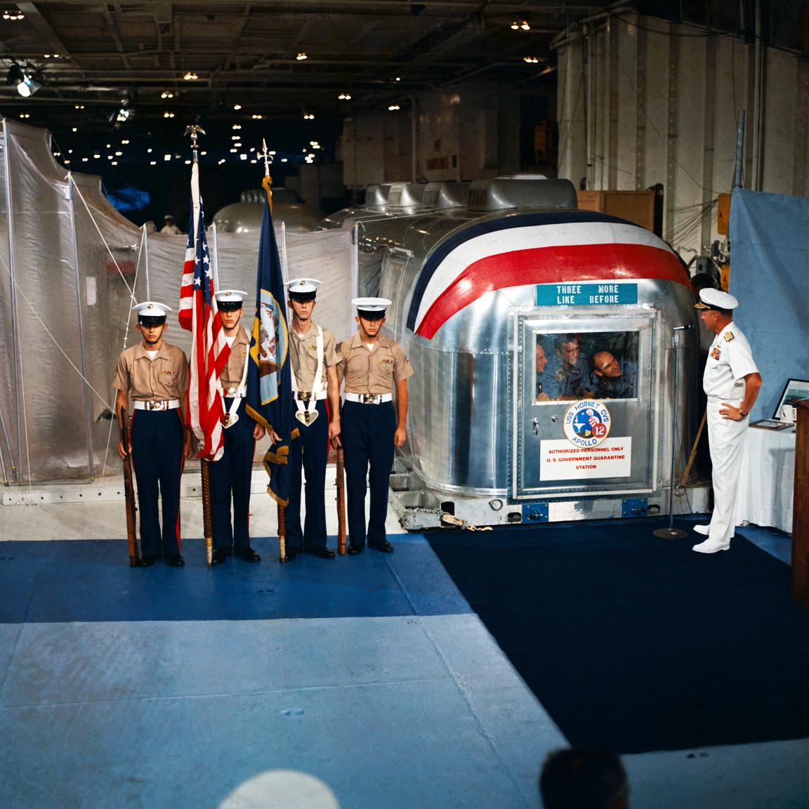 1969. november 24. Donald C. David admirális üdvözli a Holdról visszatért három űrhajóst a USS Hornet repülőgép-hordozó fedélzetén, a speciális elkülönítő-egységben.