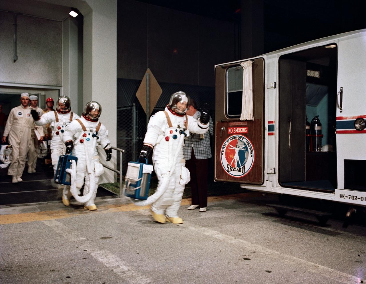 1973. július 28. A Skylab-3 legénysége beszáll a startállásra vivő kisbuszba. Az élen Bean, mögötte Garriott és Lousma.