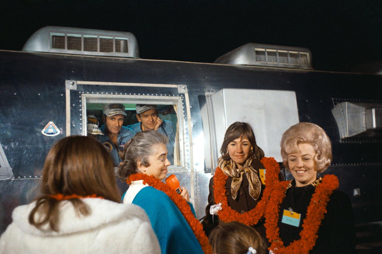 1969. november 29. A Holdról való visszatérés után még mindig karanténban lévő űrhajósok és feleségeik az Ellington légibázison. A mobil elkülönítőben balról jobbra: Conrad, Gordon  és Bean. A virágfüzért viselő feleségek balról jobbra: Mrs. Barbara Gordon, Mrs. Jane Conrad és Mrs. Sue Bean.