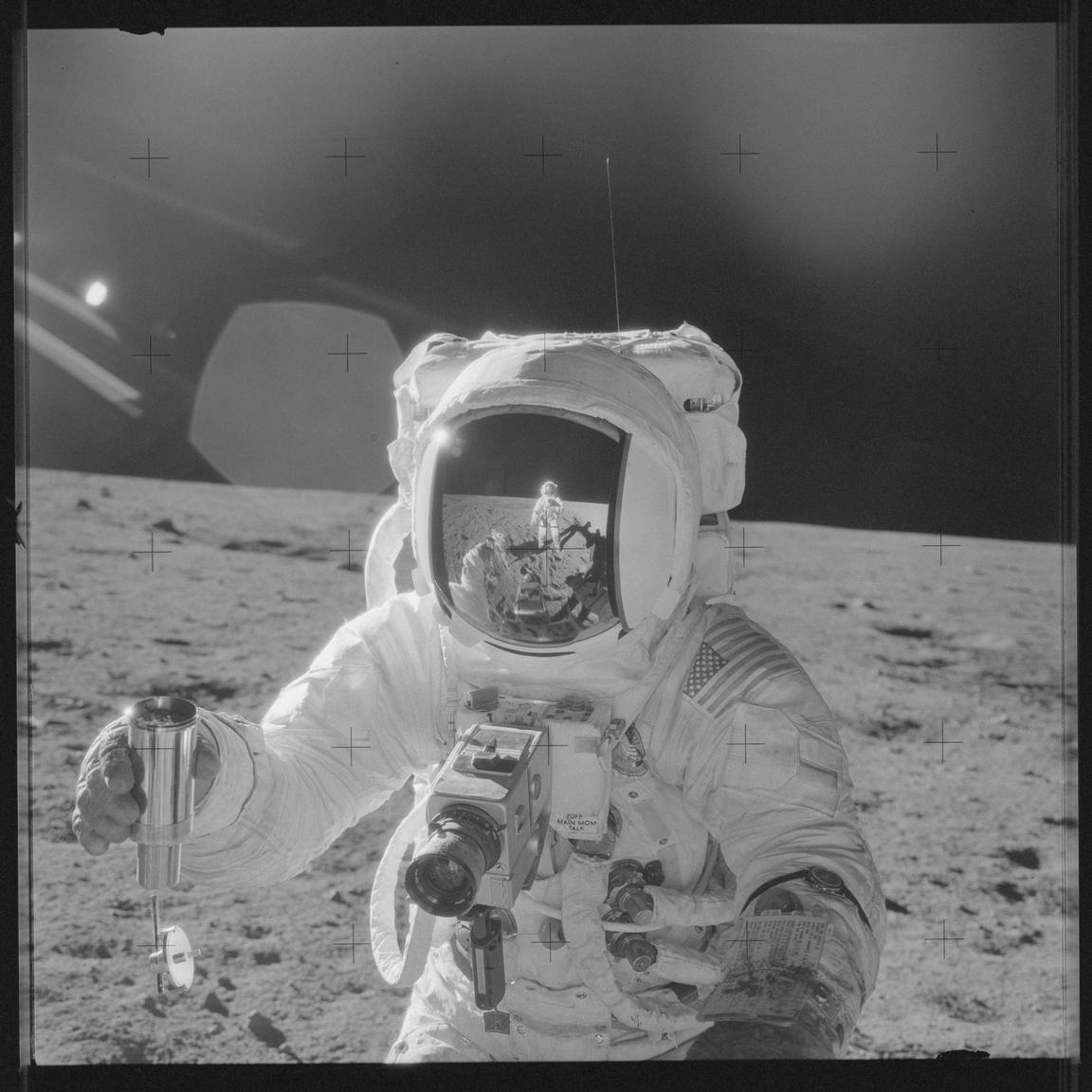 1969. november 20. Talán a legütősebb kép Beanről a Holdon. Itt épp egy fém mintavevő tartályt fog jobb kezében, sisakja fényvédő rostélyában a fotót készítő Pete Conrad alakja tükröződik.