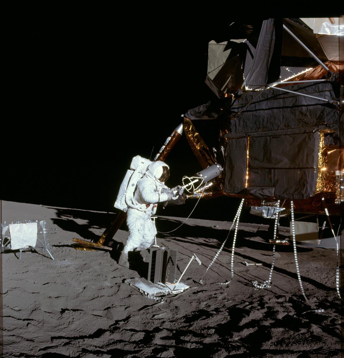 1969. november 19. Bean az első holsétán, épp leszereli a holdkompról a radioizotópos termoelektromos generátor (Radioisotope Thermoelectric Generator, RTG) üzemanyagtartályát. Az RTG a Hold felszínére telepített műszereket, kísérleti felszerelést (Apollo Lunar Surface Experiments Package, ALSEP) látja el energiával.