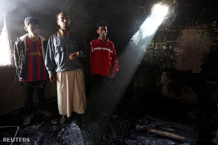 Kadhafihoz hű civilek mutatják lakásukban a nemzetközi erők légicsapásának eredményét