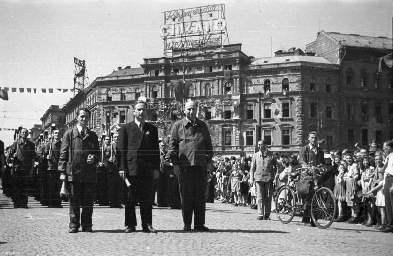 """1946. május elsejei felvonulás. A kalapácsos munkások feje fölött a szlogen: """"Kérjen eredeti Cinzano vermouthot"""". A szovjethatalom már a kanyarban, a hanyatló nyugat termékét reklámozó neonnak nem sok van hátra. Az épület sarkán egy Törley pezsgőt hirdető neon látható még."""