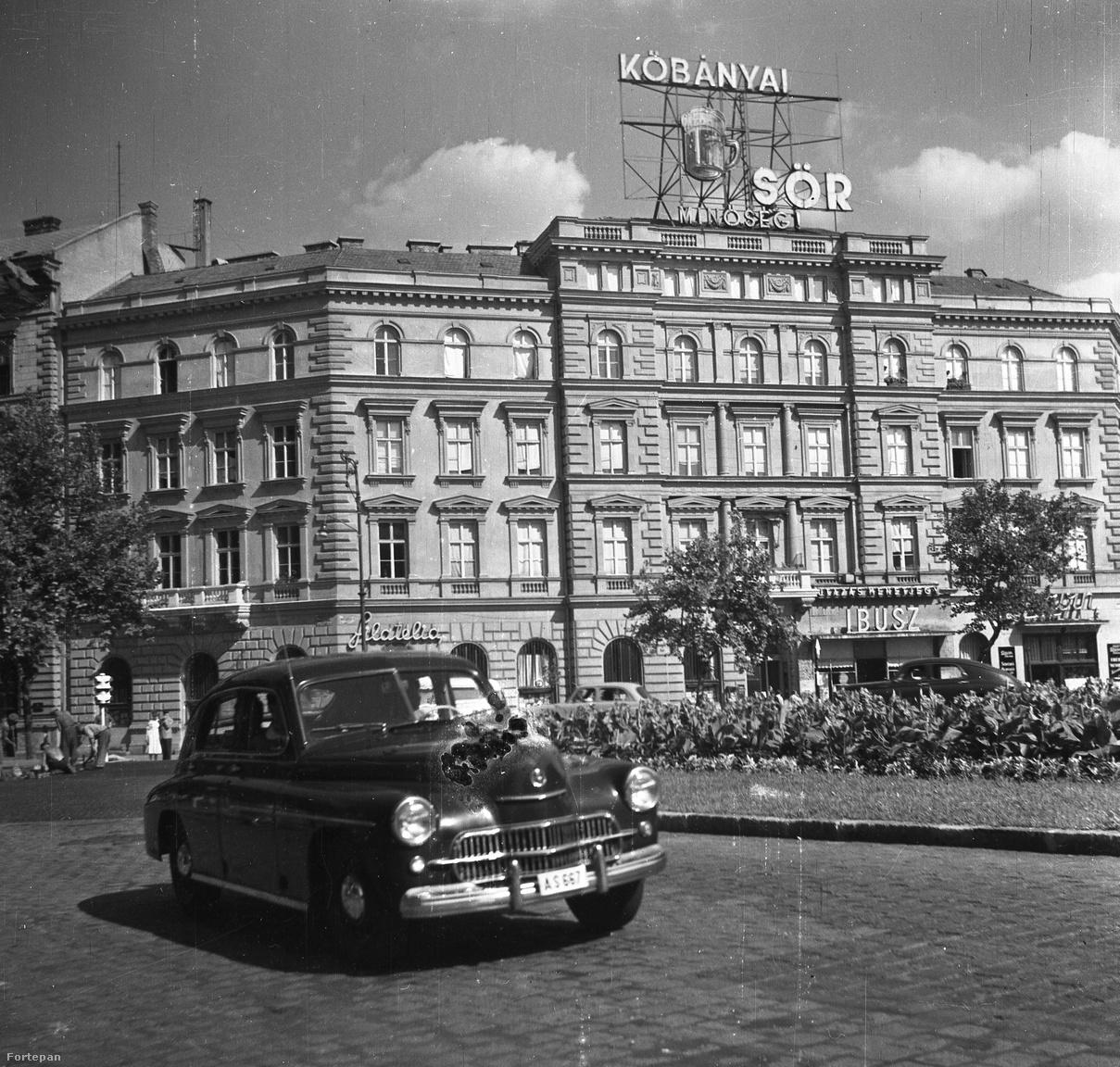 1958: a November 7. téren áthaladó Warszawa M-20 típusú személygépkocsi fényét a Kőbányai (már nem Polgári) Sör reklámja emeli. Az Ibusz utazási iroda portálja is saját neont kapott, és mint látható, a Claridge kávéház helyén Filatélia bolt nyílt, a bélyeggyűjtők legnagyobb örömére.