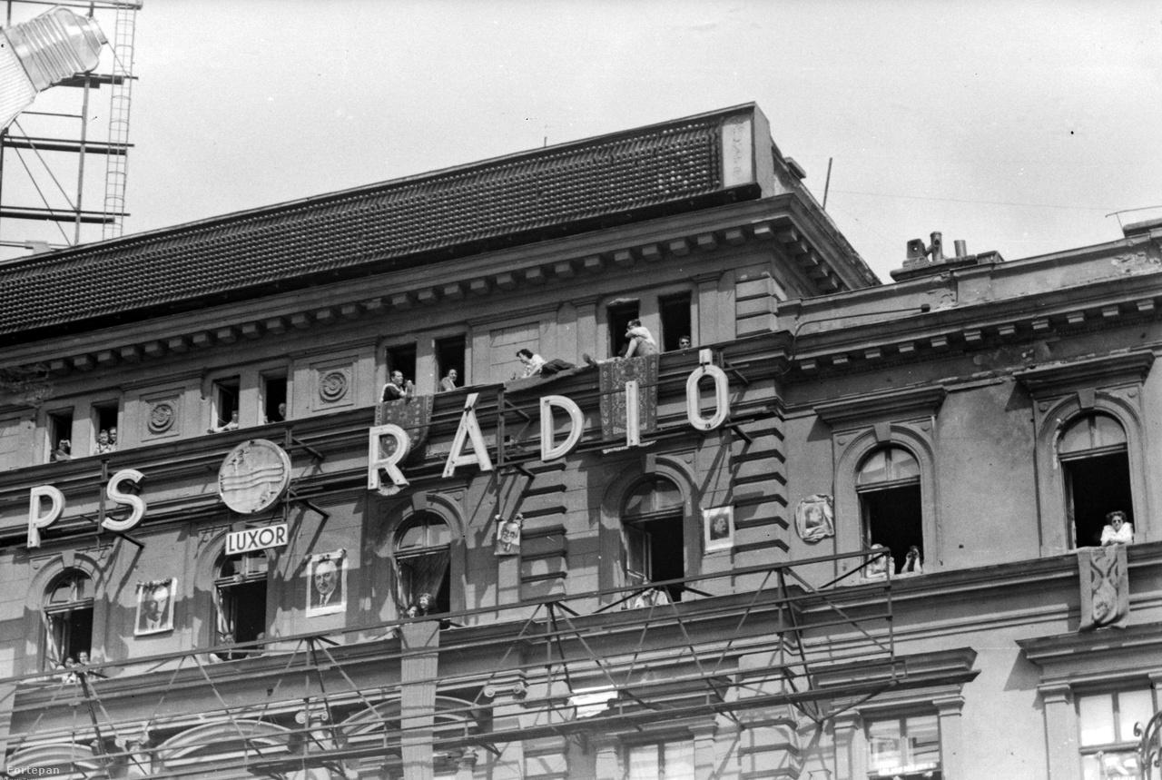 1949: a Philips Rádió – amit hazánkban is gyártottak licensz alapján – neonja még tartja magát, de a sötét Rákosi-kor közeledtét jelzik a politikusi arcképek a ház homlokzatán. Bal szélen az új neonnal jelentkező Tungsram villanykörtéjének sarka lóg be.