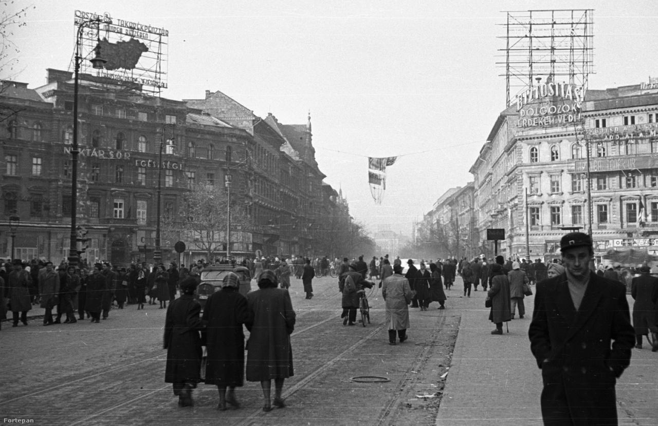 """Az Oktogon az ötvenhatos forradalom idején. Az OTP neonja (a fotó bal fölső sarkában) ezt üzeni: """"Országos Takarékpénztár – az ország minden részében a lakosság rendelkezésére áll"""". A lakosság egy jelentős része pár hét múlva elhagyja az országot."""