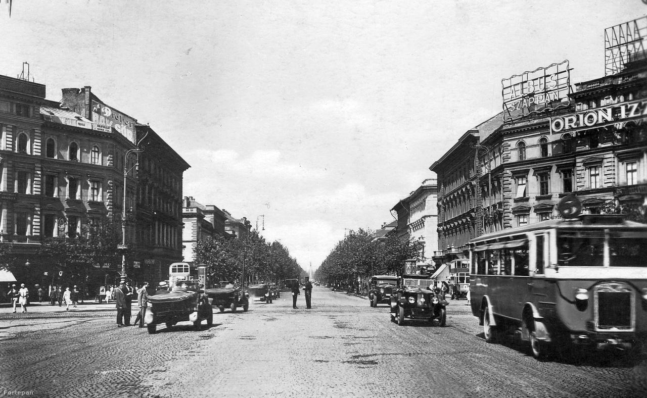 """1929. Az Oktogon a Hősök tere felé nézve. Jobbra """"Albus szappan"""" és """"Orion izzólámpa"""" – két magyar termék neonreklámja. A taxik és autómobilok közt egy Mávag NAG 204 magyar gyártmányú autóbusz feszít a kép jobb szélén."""
