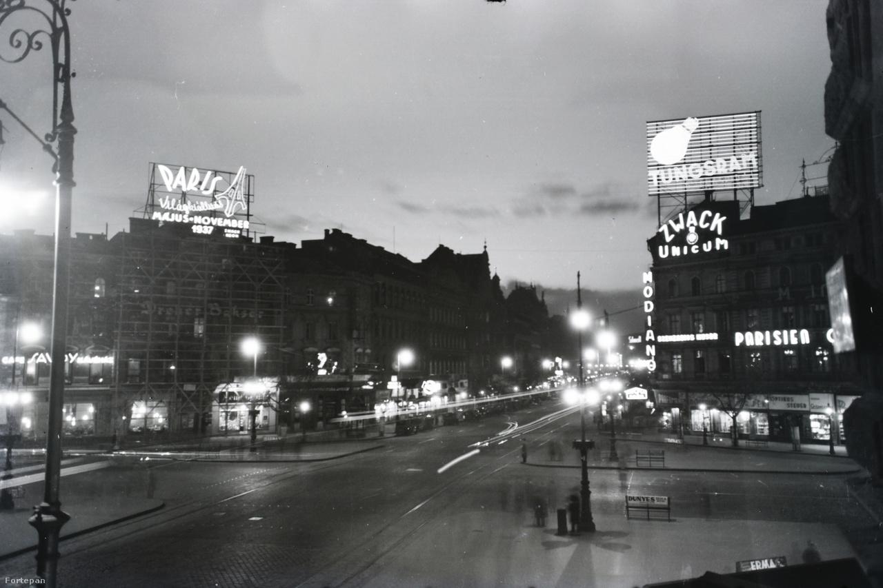 1937 körül készülhetett ez a körfotó, legalábbis bal oldalt a Párizsi Világkiállítás neonreklámja erre utal. A teret a Tungsram hatlamas tetők fölé magasodó neonja uralja, a Zwack unicum és a Modiano cigaretta reklámja fölött. A margitszigeti Parisien Grill Revue Dancing mulató neonja szenzációs műsort ígér. Balra lent a Savoy Kávéház neonja látható még.