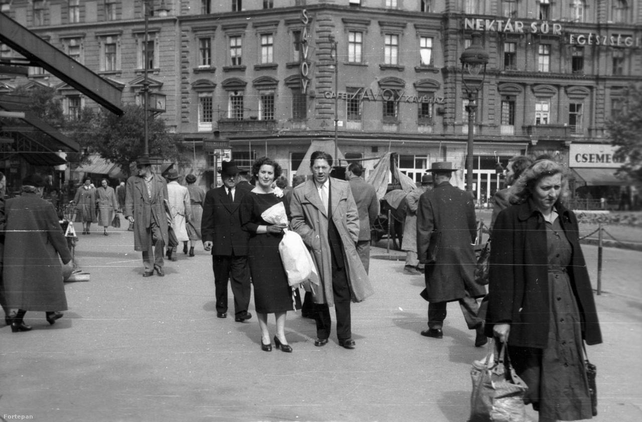 Kicsit ereszkedjünk le a járókelők közé ennek az 1946-ban készült kép segítségével. A fotós az Abbázia kávéház felől a Savoy kávéház felé nézve örökítette meg az elegáns, virágcsokros párt. Jobbra fölül egy a Nektár Sör egészségességét hirdető neon látható.