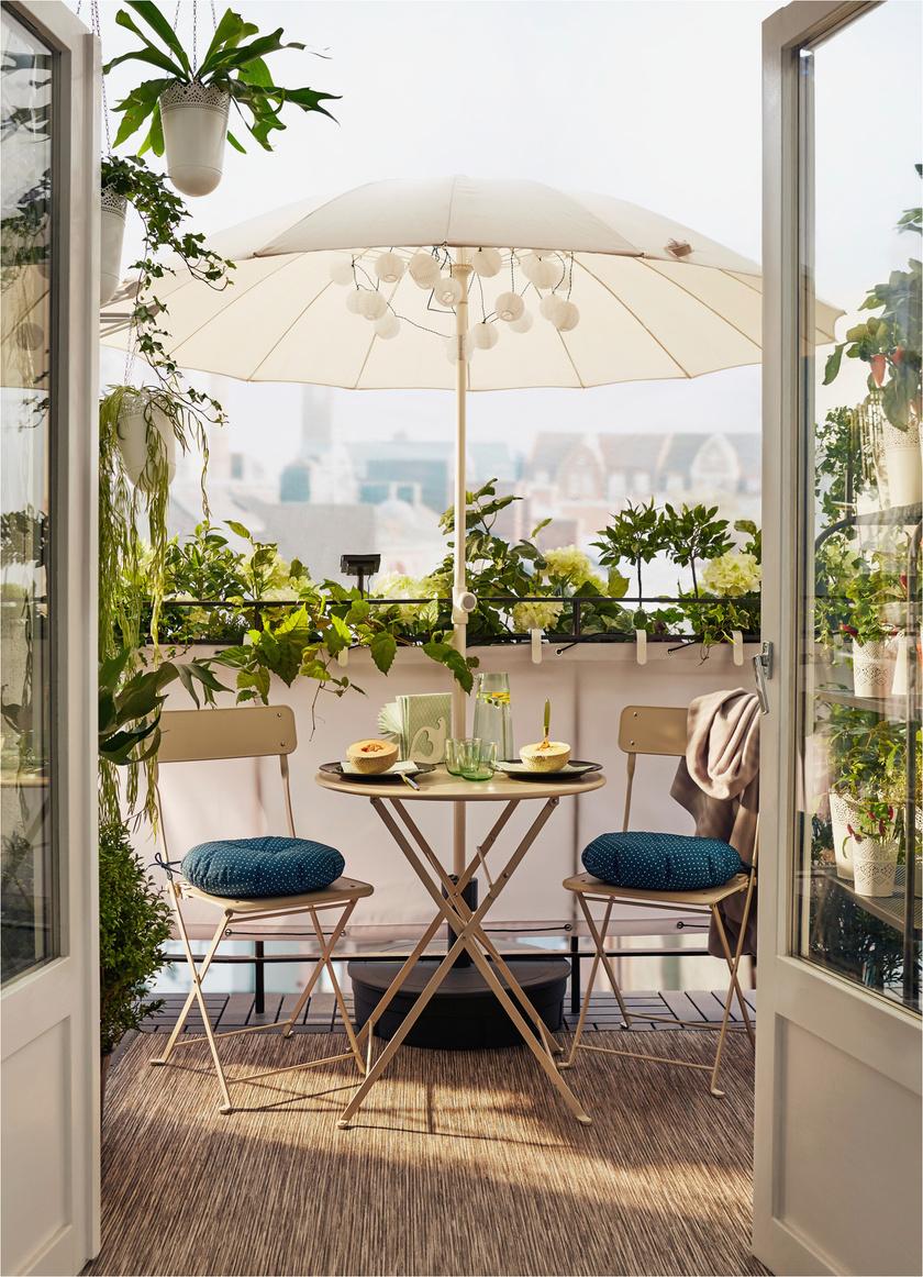 Gyönyörű megoldás: változatos, zöld növények övezik az erkélyt, miközben a tűző naptól ernyő véd.