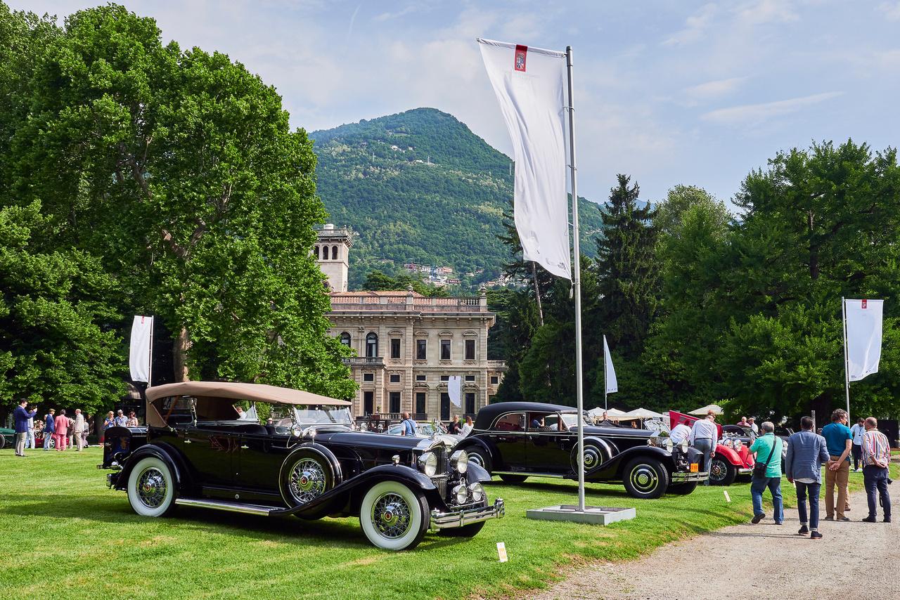 """Packard Standard Eight, 1932 és Rolls-Royce Phantom II, 1933. Vasárnap reggeli látkép a Villa Erba területén, mielőtt ellepi a tömeg. Ez a két kocsi is """"Az autós gazdagság aranykora"""" kategóriában indult. A Packard a közelmúltban hibátlanul végigment egy 1200 mérföldes, 14 százalékos emelkedőkkel tűzdelt túrán, 38 fokban. Azt nem tudni, hány ilyen Rolls készült, valószínűleg legalább kettő, legfeljebb négy."""