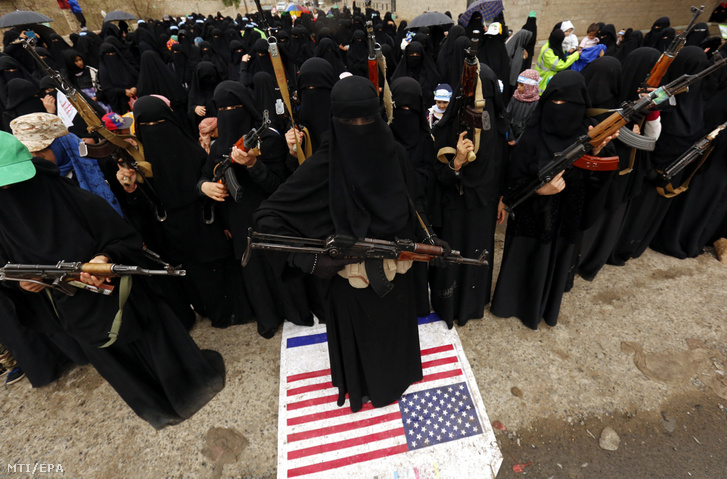 Gépfegyveres jemeni nők tüntetnek egy amerikai zászlón taposva a Szaúd-Arábia vezette nemzetközi szövetség légicsapásai ellen a jemeni fővárosban, Szanaában 2018. április 7-én.