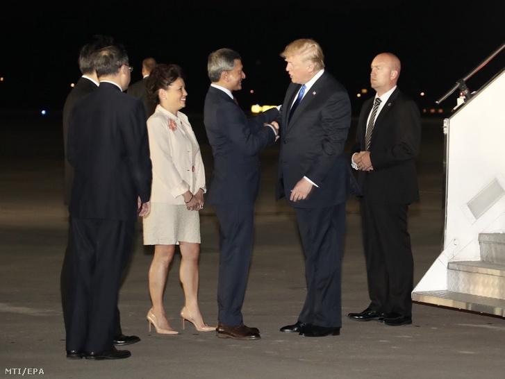 Vivian Balakrishnan szingapúri külügyminiszter (j3) üdvözli Donald Trump amerikai elnököt (j2) a szingapúri Paya Lebar katonai repülőtéren 2018. június 10-én.