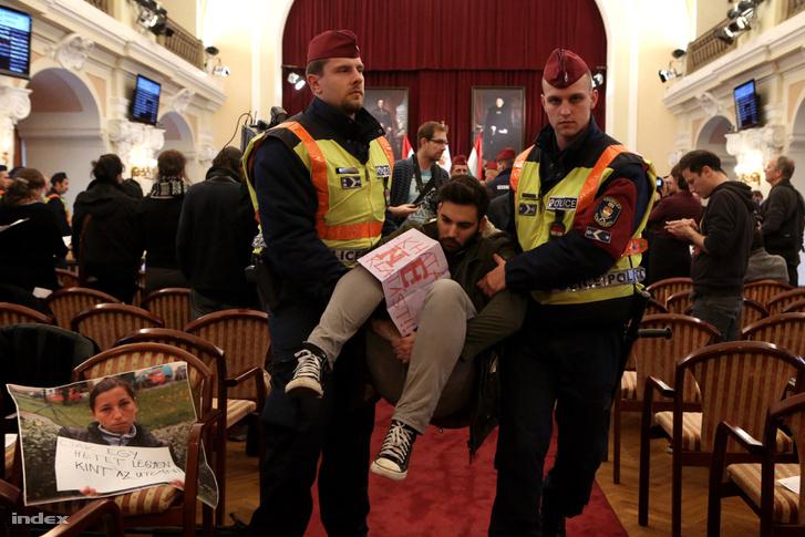 A Város Mindenkié csoport aktivistáit viszik ki a rendőrök a fővárosi közgyűlés üléséről 2013. november 14-én, amikor a közgyűlés arról döntött volna, hogy Budapest bizonyos közterületein nem tartózkodhatnak hajléktalanok életvitelszerűen.