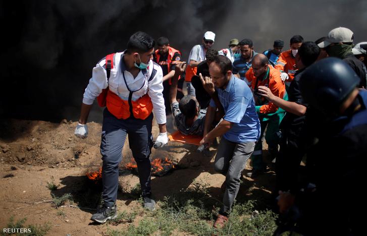 Sebesült palesztin tüntetőt visznek el az izraeli határról 2018. június 8-án
