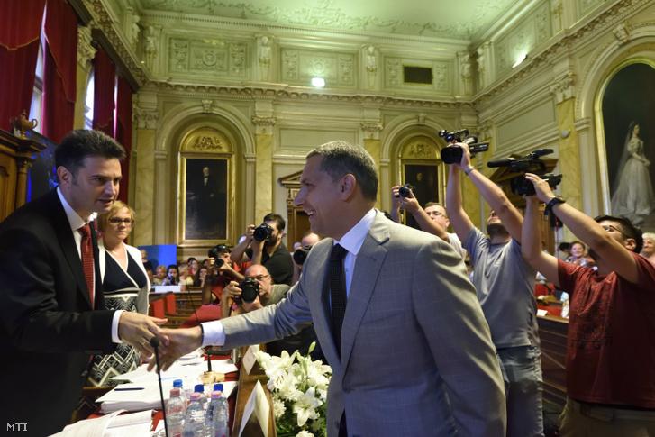 Márki-Zay Péter (független) polgármester (b) és Lázár János, a térség fideszes országgyűlési képviselője kezet fog a hódmezővásárhelyi közgyűlés ülésén 2018. május 29-én.