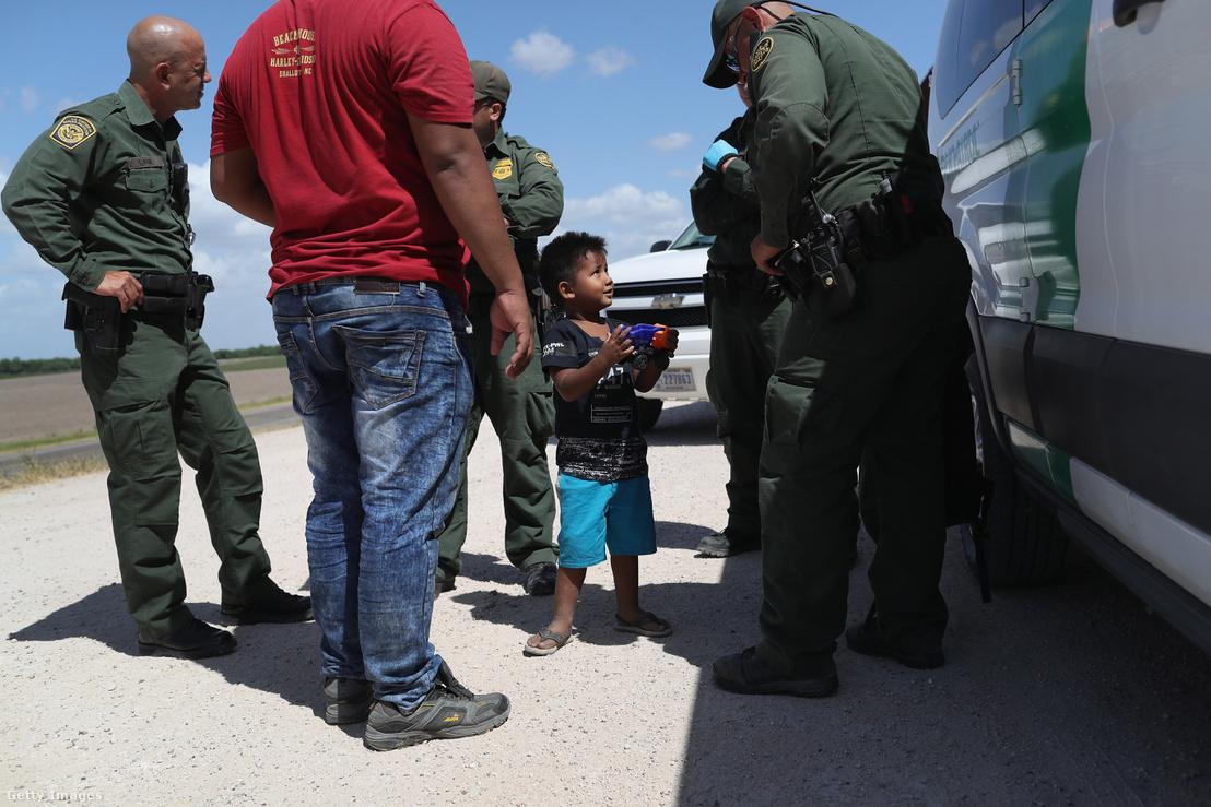 Egy Hondurasból érkező fiú mutatja a játékát az amerikai határőröknek
