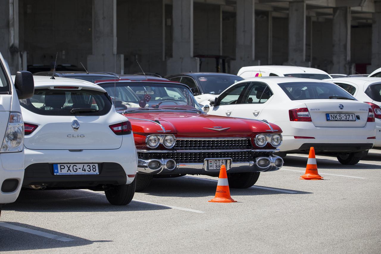 A  sok modern, fehér egyendoboz között lapuló, gyönyörűen karbantartott, dögös vörös Cadillac Deville-nél nem sok feltűnőbb jelenséget lehetett látni a parkolóban.                         12. Szerencsés férfi lehet, akinek ez a grid girl tartja a zászlóját