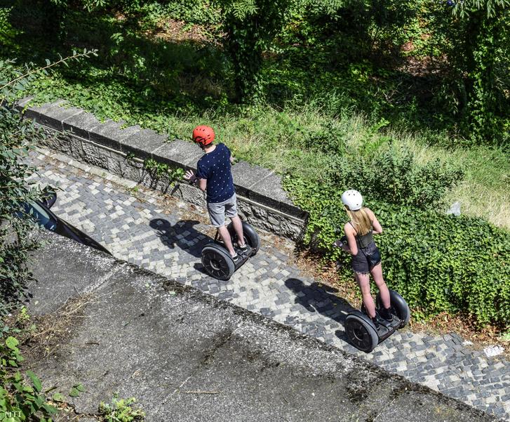 Két fiatal segwayjel közlekedik a budai várba vezetõ emelkedõ úton.