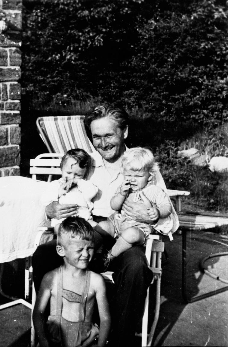 """Németh László unokáival sajkodi házukban, 1960 körülAz író 1957 márciusa óta az év nagy részét itt töltötte, eleinte fordítással és tanulmányírással, hiszen a  forradalom leverése és a népi írók elleni támadások mást nem tettek lehetővé. Németh László lánya és veje 1954-ben egy balatoni kiránduláson találta meg a sajkodi telket, és vágott bele az építkezésbe. """"A rá következő nyár végén már a fákat is elültették a nyaraló körül, hogy a harmadik őszön innen induljanak el a határ felé. A lányom, aki biciklin hordta az építkezéshez a cementes zsákot, kilenc év múlva mint kanadai vendég látta viszont a megnőtt növényeit""""– sűrítette Németh László egyetlen történetbe a történelem fordulatait."""