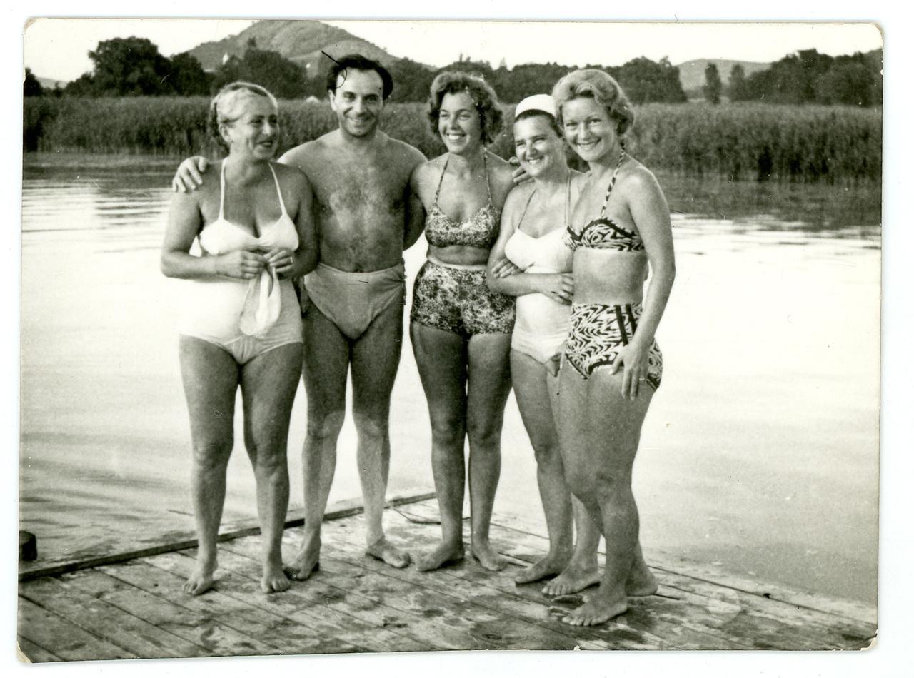 """Devecseri Gábor és balján felesége, Huszár Klára ismeretlenek között a szigligeti íróstégen, 1965 körül.Devecseri és Karinthy Ferenc, a két Lágymányoson együtt nevelkedett cimbora adta meg Szigliget máig emlegetett legendás hangulatát. Az utánzások, a """"szeretetteljesen gyilkos szatírák"""", a szójátékok a Hadik kávéház teraszáról nőtték ki magukat, ahogy csínyeik és csábításaik is. Devecseri """"soha életében egy cigarettát el nem szívott, szeszes italba ugyan társaság kedvéért olykor belekortyolt, de nem ízlett neki se bor, se rövid ital […], mégis mindig úgy tetszett, hogy mámoros állapotban van: szerelemtől, költészettől, egy sajátos nyelvtani igealaktól vagy éppen egy izgalmas pletykától."""""""