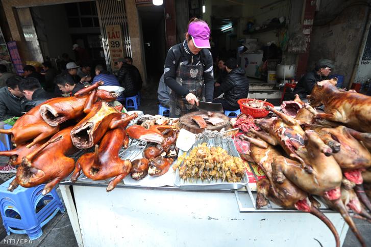 Emberi fogyasztásra szánt egyben sütött kutyahúst darabol egy vietnami árus egy hanoi piacon 2018. február 13-án három nappal a holdújév a Tet elõtt.