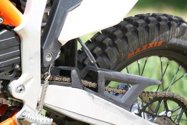 A kép közepén lévő, látszólag funkciótlan gumiizé az utcai motoros számára ismeretlen: oda lehet felkötni az oldaltámaszt, hogy menet közben véletlenül se nyíljon le