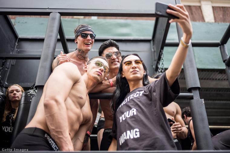 Ezen a képen Alexander Wang divattervező látható pólóban, modelljeivel szelfizik éppen.