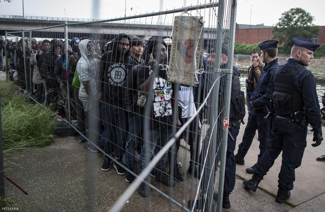 Menekültek várakoznak elszállításukra a Millenium néven ismert sátortáboruk felszámolása közben Párizs egyik külső kerületében 2018. május 30-án.