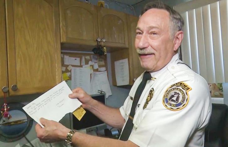 Michael Combs rendőr kezében a levéllel és a 44 éves bírságértesítővel