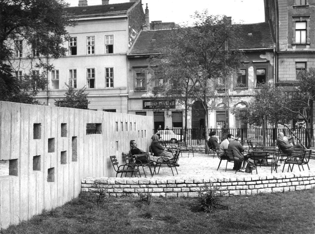 Ez is a Klauzál tér. Ma már ilyen székek legfeljebb egy büfé mellett képzelhetők el, de akkoriban parkokban is előfordultak. Mai szemmel nézve szinte őrizetlenül. Sőt! Sok helyen ugyanígy lehetett találkozni kihelyezett napágyakkal, amelyek a kor emblematikus köztéri tárgyai voltak sok helyen.