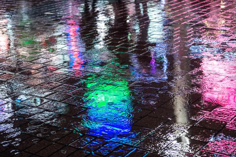 Esős aszfalt tükröződő neonfényekkel a shibuya kereszteződés mellett