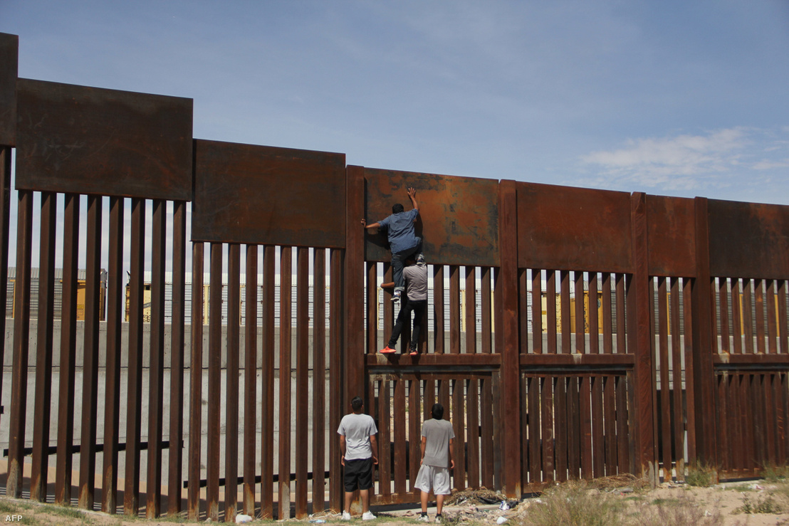 Illegális határátlépők próbálják megmászni a falat az amerikai határon.