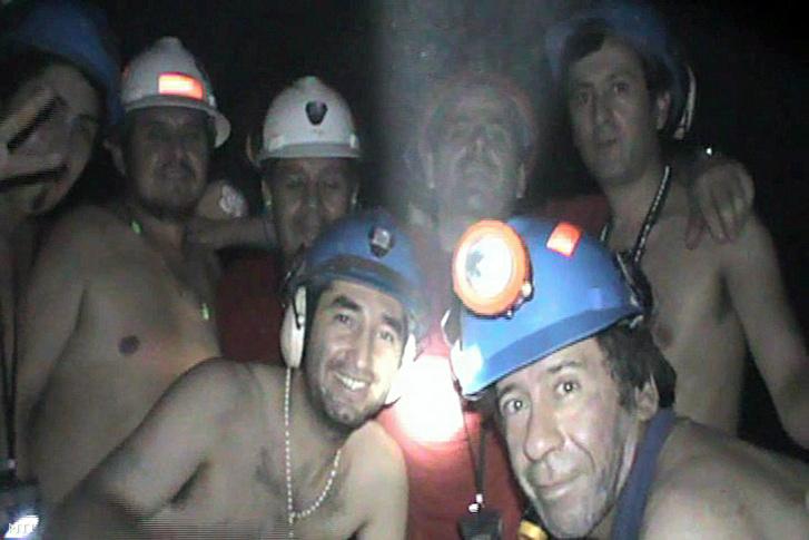 A copiapói San José réz- és aranybányában rekedt bányászok egy csoportja mosolyog a videokamerába 2010. szeptember 17-én. Ezen a napon a mentésen dolgozó egyfúrófej elérte azt a helyet, ahonnan a bányászokat fel tudják majd húzni. A bányában augusztus 5-én bekövetkezett omlás miatt 700 méteres mélységben a föld alatt rekedtek a bányászok.